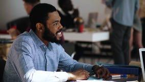 Homem preto considerável novo de sorriso feliz do gerente do close-up que fala ao colega na tabela multi-étnico do escritório do  filme