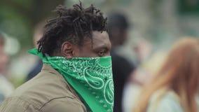 Homem preto do gângster no facemask verde que olha ao redor no evento aglomerado do verão video estoque