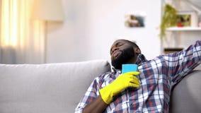 Homem preto esgotado nas luvas que encontram-se no sofá, relaxando após a limpeza da casa fotografia de stock