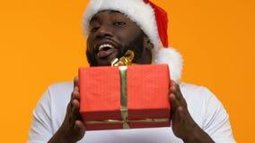 Homem preto feliz no chapéu de Santa que mostra a caixa atual vermelha, feriados comprando, venda filme