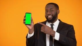 Homem preto no terno que aponta no smartphone prekeyed, lugar para a propaganda video estoque