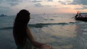 Homem principal da jovem mulher na praia no ponto da câmera da ação do por do sol do vew da menina de sorriso feliz no beira-mar filme