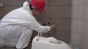 Homem profissional do encanador que prepara-se para a montagem da bacia da bandeja do toalete no banheiro novo video estoque