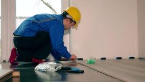 Homem profissional do trabalhador que coloca o assoalho estratificado de madeira no apartamento novo vídeos de arquivo