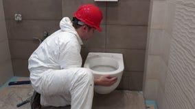 Homem profissional do trabalhador que pendura a bandeja pesada da bacia de toalete no banheiro moderno novo filme