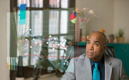 Homem profissional que revê uma carta futurista em seu escritório imagens de stock royalty free