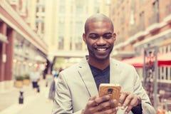 Homem profissional urbano de sorriso feliz que usa o telefone esperto