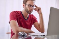 Homem profundamente na concentração na frente do computador Fotos de Stock Royalty Free
