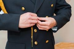 Homem que abotoa um uniforme Imagens de Stock