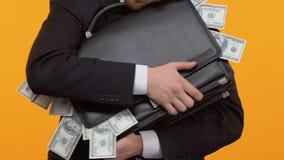 Homem que abraça sua pasta com colagem para fora do dinheiro, corrupção, subôrno, close-up filme