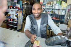 Homem que aceita o pagamento do cartão do cliente imagens de stock