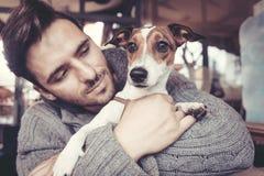 Homem que afaga com seu cão no inverno imagem de stock