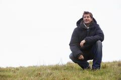 Homem que agacha-se no parque Imagem de Stock Royalty Free