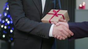 Homem que agita as mãos e que guarda um presente do Natal video estoque