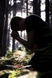 Homem que ajoelha-se e que praying na floresta Fotos de Stock Royalty Free