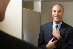 Homem que ajusta o laço no espelho imagens de stock royalty free
