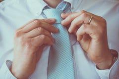 Homem que ajusta seu laço Imagem de Stock