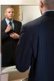 Homem que ajusta seu laço no espelho foto de stock