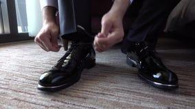 Homem que amarra laços em sapatas pretas caras