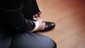 Homem que amarra sapatas de couro envernizado video estoque