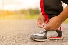 Homem que amarra sapatas na borda da estrada Ou homem do esporte que amarra sapatas fotos de stock royalty free