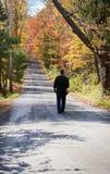 Homem que anda abaixo da estrada Foto de Stock Royalty Free