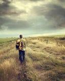 Homem que anda abaixo da estrada secundária Fotografia de Stock
