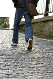 Homem que anda acima de uma estrada do cobblestone Fotografia de Stock Royalty Free