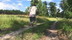 Homem que anda afastado em um trajeto da terra do verão com os pés descalços vídeos de arquivo