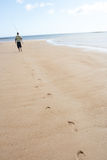 Homem que anda ao longo da pesca carreg Rod da costa Fotografia de Stock Royalty Free