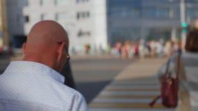 Homem que anda através da multidão de povos na cidade grande Cruzando a rua Feche acima do tiro filme