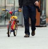 Homem que anda com bicicleta da criança foto de stock