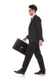 Homem que anda com pasta & que olha afastado Foto de Stock Royalty Free