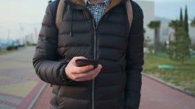 Homem que anda com smartphone fora vídeos de arquivo
