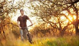 Homem que anda com uma bicicleta Imagens de Stock Royalty Free