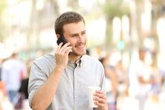 Homem que anda e que fala no telefone celular Fotografia de Stock Royalty Free