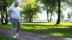 Homem que anda lentamente, esgotado após a corrida, cardio- treinamento para a perda de peso fotografia de stock