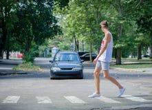 Homem que anda na frente de um carro Uma rua do cruzamento do menino em um fundo borrado Cuidadoso no conceito da estrada Copie o Fotos de Stock