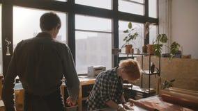 Homem que anda na oficina de fabricação, artesão fêmea do movimento lento que corta o couro em uma tabela para bens feitos a mão filme