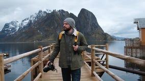 Homem que anda na ponte de madeira Os fiordes noruegueses silenciosos Montanha do fundo video estoque