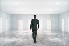 Homem que anda na sala com portas Imagem de Stock Royalty Free