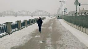 Homem que anda no beira-rio do inverno, filmado de um zangão que move-se afastado na frente dele video estoque
