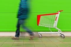Homem que anda pelo trole vazio do carrinho de compras Foto de Stock