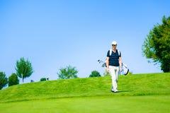 Homem que anda a sua bola de golfe imagem de stock royalty free
