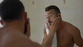 Homem que aplica a loção de aftershave para enfrentar no banheiro, prevenção da seca da pele video estoque