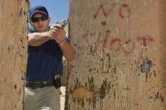 Homem que aponta a arma da mão na escala de acendimento Foto de Stock Royalty Free