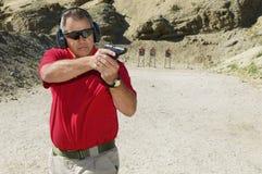Homem que aponta a arma da mão na escala de acendimento Imagens de Stock