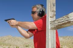 Homem que aponta a arma da mão na escala de acendimento Fotografia de Stock Royalty Free