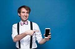Homem que aponta com o dedo ao smartphone com a tela vazia no fundo azul imagem de stock royalty free