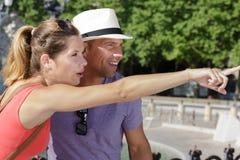 Homem que aponta em algo ao sightseeing com amiga imagens de stock royalty free